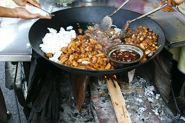 One's frying the koay, the other's cutting fresh pieces into the wok, which is fired by charcoal and wood.