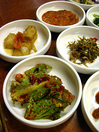 Clockwise from one o'clock: kimchi pancake; fried anchovies; lettuce with sweet spicy dressing; fried tofu.